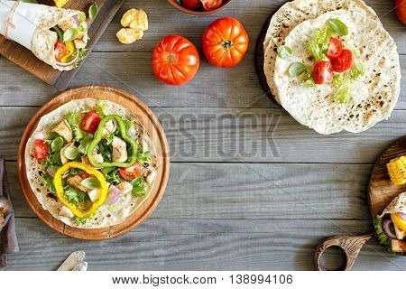 Tortilla with grilled chicken fillet and vegetables on wooden table with copy space. Top view. Outdoors Food Concept
