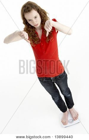Unhappy Young Girl Standing On Scales