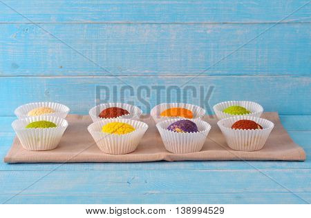 Set of different colorful cake shu eclairs on a blue wooden table with copy space