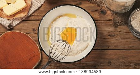 Flour in a bowl with egg yolk close up on a wooden table top view