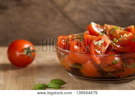 Tomato salad with basil olive oil and balsamic vinegar in bowl over wooden background