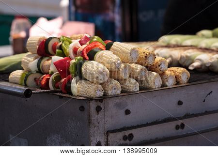 Corn, pepper and onion kabobs on a barbecue grill cooking at a fair ground.