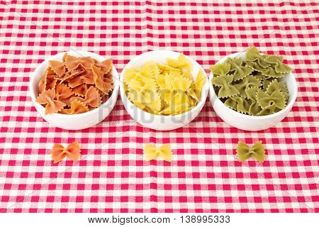 Pasta farfalle in bowls on red tablecloth