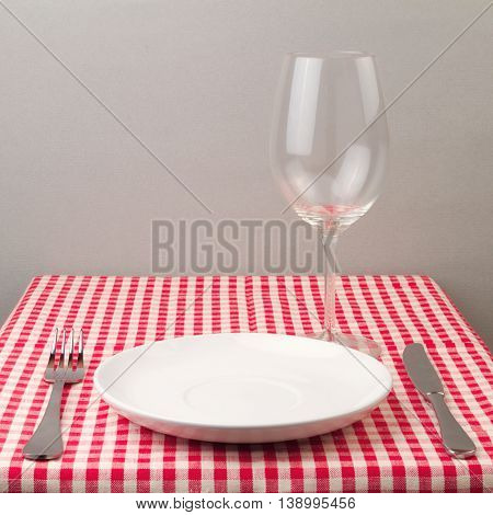 Setting with plate silverware and wine glass on table with tablecloth