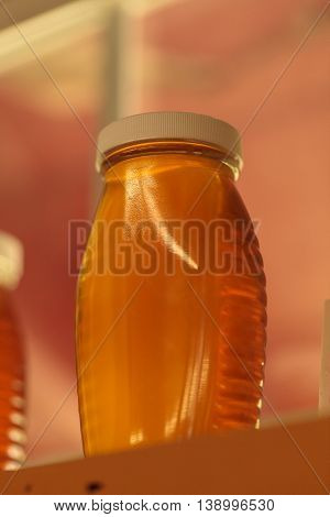 Jar of organic honey freshly harvested from local honeybees on a farm.