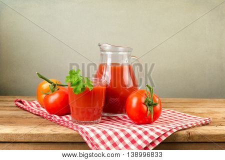 Red tomato juice with tomatoes on wooden table