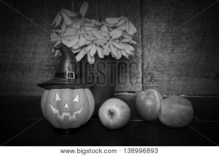 halloween set pumpkin doll and apple on wooden background black vignette black and white tone