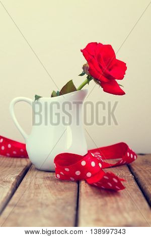 Red rose with polka dots ribbon in a white vase