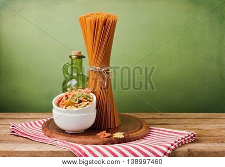Whole wheat spaghetti and farfalle pasta on wooden table