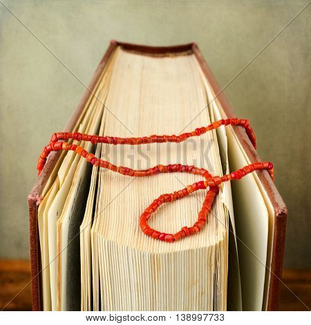 Book with coral necklace over grunge background
