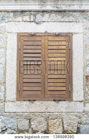 Old closed wooden window on the stone wall.