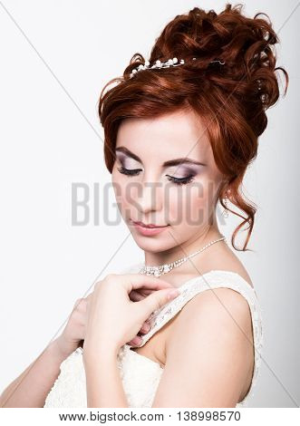 close-up portrait of young beautiful bride in a wedding dress with a wedding makeup and hairstyle