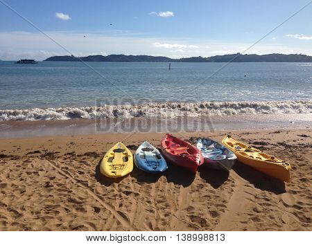 Colorful kayaks on a sandy beach at Paihia Bay of Islands New Zealand NZ.