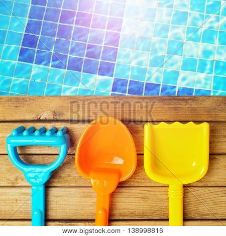 Summer toys on wooden deck over swimming pool