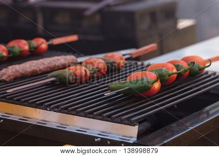 Pepper and tomato kabobs on a barbecue grill cooking at a fair ground.