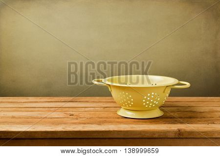 Empty colander on wooden deck table over grunge background