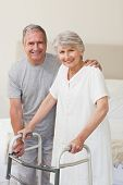 stock photo of zimmer frame  - Man helping his wife to walk - JPG