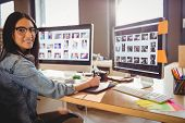 Female graphic designer using graphic tablet while working on computer at office poster