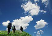Three tourist going up along grassland poster