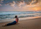 Постер, плакат: Yoga outdoors on beach woman practices Ashtanga Vinyasa yoga Surya Namaskar Sun Salutation asana U
