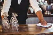 Mid section of bartender cleaning a bar counter with napkin poster