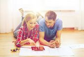 repair, building, renovation and home concept - smiling couple looking at tablet pc at home poster