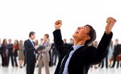 foto of woohoo  - One very happy energetic businessman with his arms raised - JPG