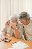 Sad mature couple calculating their domestic bills poster