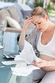Worried pregnant woman calculating her domestic bills at home poster