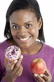Woman Choosing Between Apple And Doughnut