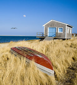image of cape-cod  - A traditional New England dory rests in front of a boat house at Cotchpinicut in Chatham Massachusetts.  - JPG