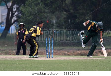 PUCHONG, MALAYSIA - SEPT 24: Malaysia's MN Azril nicks the bails as Guernsey's Ben Ferbrache just made it, at the Pepsi ICC WCL Div 6 finals in Kinrara Oval on Sept 24, 2011 in Puchong, Malaysia.