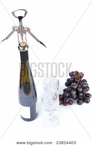 Bottle of wine with aperitive glasses and grapes isolated in white