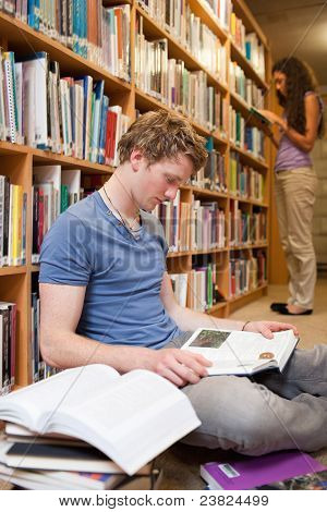 Portrait Of A Male Student Reading Books While His Classmate Is