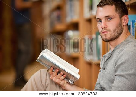 Serious Male Student Holding A Book