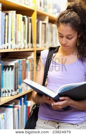 Portrait Of A Serious Female Student Reading A Book