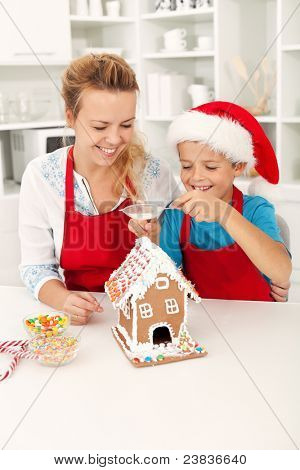 Final touches on the gingerbread house - people at christmas time in the kitchen