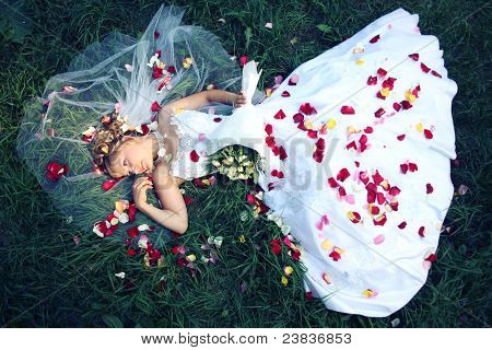 Bride Lying On The Grass And Rose Petals
