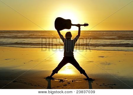 Guitar player with sunset at the beach