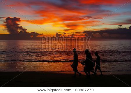 Walking On The Beach At Sunset