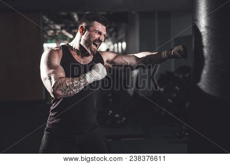 poster of Bearded Male Boxer Training With Punching Bag In Dark Sports Hall. Young Tattoed Boxer Training On P
