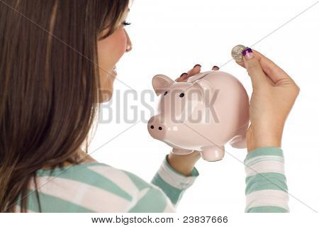 Over Shoulder of a Pretty Smiling Ethnic Female Putting a Coin Into Her Pink Piggy Bank Isolated on a White Background.