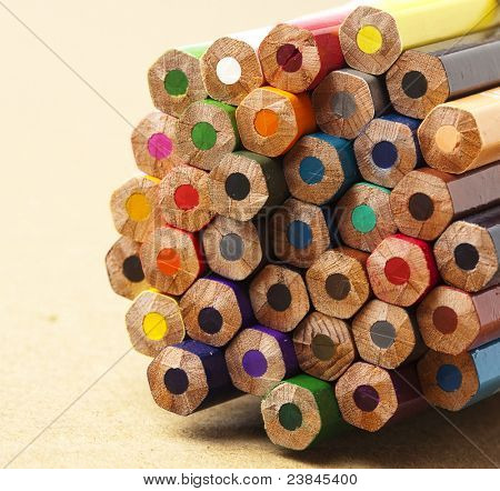 wooden crayon stack on wooden surface, extreme closeup