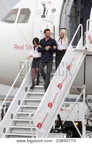 LOS ANGELES - SEPT 23:  Hugh Jackman with Virgin America flight attendants arrive as Virgin America unveils new DreamWorks 'Reel Steel' plane at LAX Airport on September 23, 2011 in Los Angeles, CA