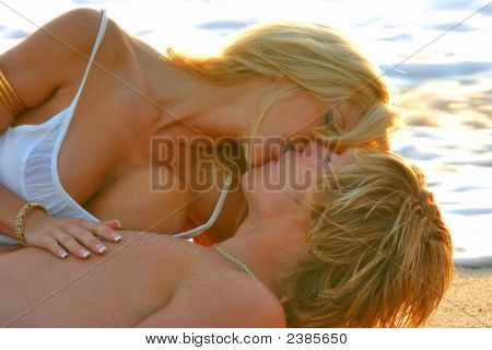 Young Couple Kissing On The Beach At Sunset.