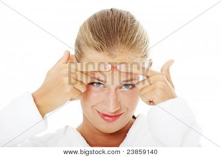 Young teenage woman with pimple on her face .Isolated on white background.