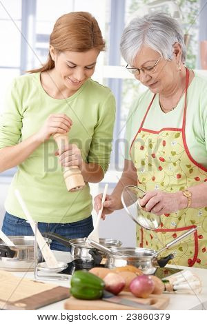 Senior mother and young daughter preparing food in kitchen, having fun, smiling.?