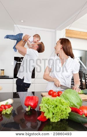 Father playing with child while mother cuts vegetables in kitchen