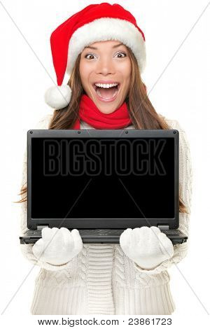 Christmas computer woman holding notebook excited wearing santa hat. Empty blank screen copy space for text. Beautiful young smiling female model isolated on white background.