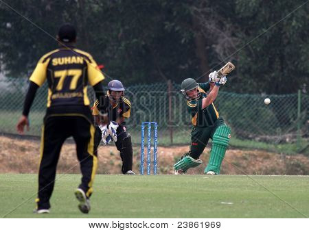 PUCHONG, MALAYSIA - SEPT 24: Guernsey's Tom Kimber bats, watched by Malaysia's Suhan (77) at the Pepsi ICC World Cricket League Div 6 finals in Kinrara Oval on September 24, 2011 in Puchong, Malaysia.